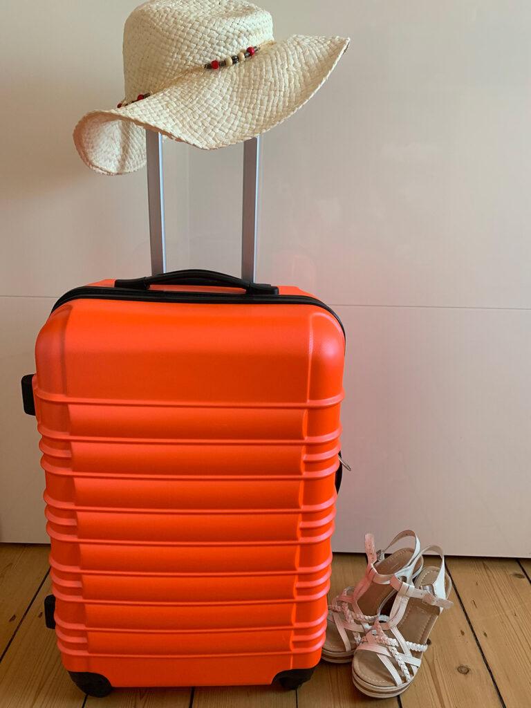 Koffer mit Sonnenhut und Sandalen