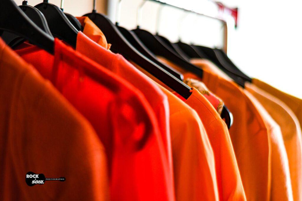 Kleidung orange auf Kleiderstange