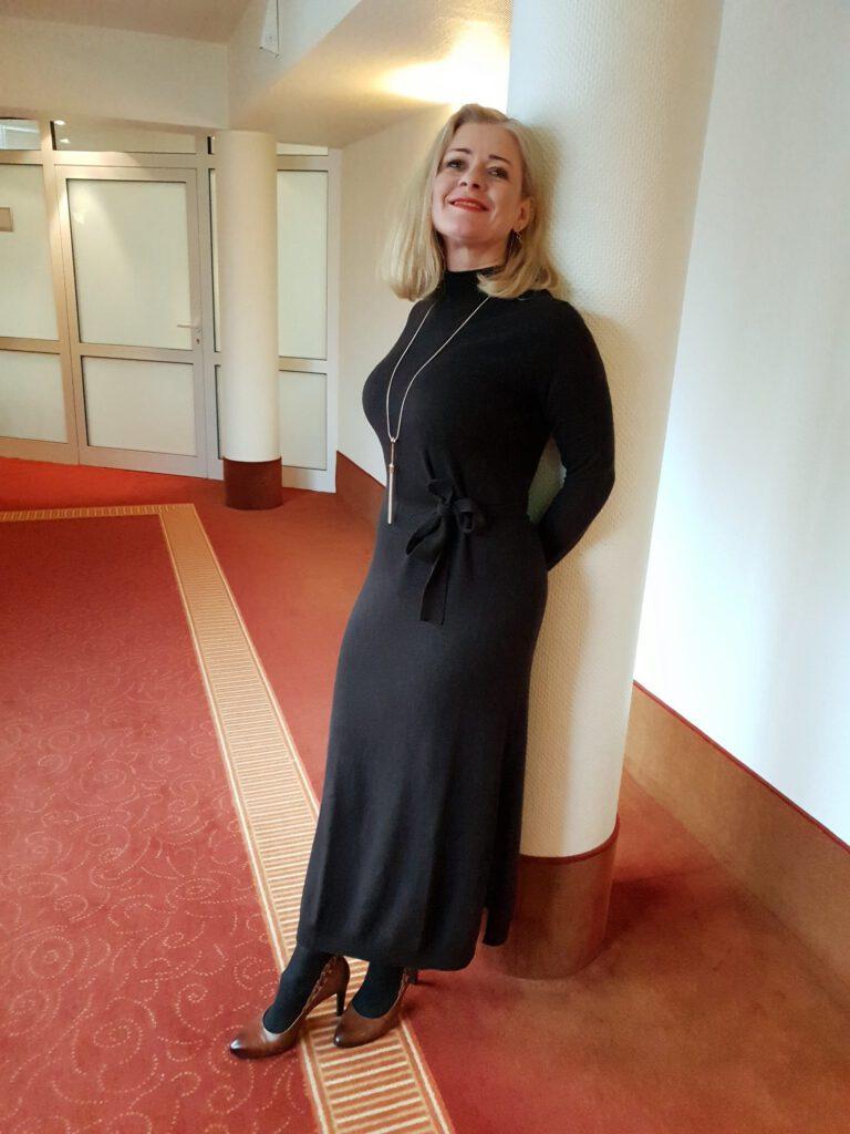 Frau langes Kaschmirkleid angelehnt an Säule
